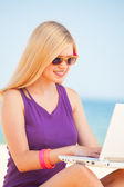 Blonde girl with notebook at the beach. — Stock Photo