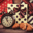 Stockfoto: Retro alarm clock with croissant on a table.