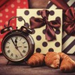 Retro alarm clock with croissant on a table. — Foto Stock