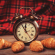 Retro alarm clock with croissant on a table. — Stock Photo #39266767