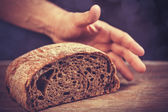 Baker's hands with a bread. — Stock Photo