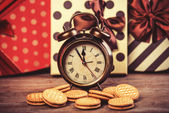 Retro alarm clock with cookie on a table. — Stock Photo