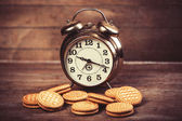 Retro alarm clock with cookie on a table — Stock Photo