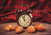 Retro alarm clock with croissant on a table. — Stock Photo