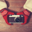 Hands in mittens holding vintage camera — Stock Photo
