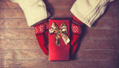Hands in mittens holding gift box — Stock Photo