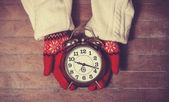 Hands in mittens holding gretro clock — Stock Photo