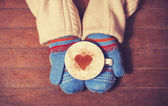 Hands in mittens holding hot cup of coffee — Stock Photo