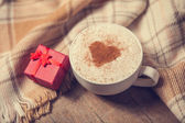 Cup with coffee and shape of the cacao heart on it and scarf — Stock Photo