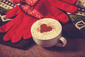 Cup with coffee and shape of the cacao heart on it and scarf. — Stock Photo