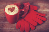 Gloves and cup with coffee and shape of the cacao heart on it. — Stock Photo
