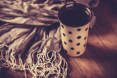 Cup of coffee and scarf on wooden table. — Stock Photo