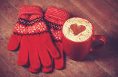 Gloves and cup with coffee and shape of the cacao heart on it. — Stockfoto