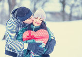 Teen couple with gift kissing in winter park. — Stock Photo