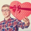 Nerd teen guy with red heart shape gift. — Stock Photo #40496213