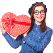 Stock Photo: Nerd girl in glasses with heart shape gift.
