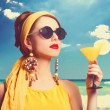 Pretty redhead women with cocktail on the beach. — Stock Photo #40496791