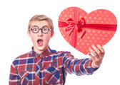 Nerd teen guy with red heart shape gift. — Stock Photo