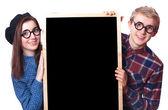 Nerd teen couple with blackboard. — Stock Photo