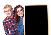 Nerd teen couple with blackboard. — Stock Photo