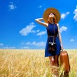 Redhead girl with suitcase at spring wheat field. — Stock Photo