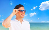Handsome young man at beach background — Stock Photo