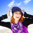 Portrait of red-haired girl with headphone on the beach. — Stock Photo