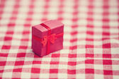 Red gift on tablecloth.  — Stock Photo