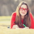 Teen girl with a pen lying down on a grass. — Stock Photo #42815059