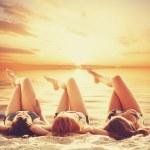 Three girls on the beach in sunset. — Stock Photo