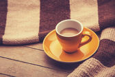 Yellow cup of the coffee and vintage scarf. — Stock Photo