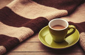Green cup of the coffee and vintage scarf. — Stock Photo
