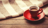Red cup of the coffee and vintage scarf. — Stock Photo