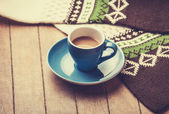 Blue cup of the coffee and vintage scarf. — Stock Photo