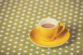 Cup of a coffe on polka dot cover. — Стоковое фото