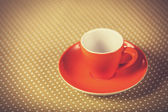 Cup of a coffe on polka dot cover. — Stock Photo