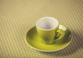 Cup of a coffe on polka dot cover. — Foto de Stock