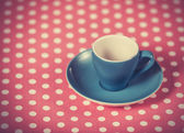 Cup of a coffee on polka dot cover. — Стоковое фото