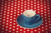 Cup of a coffee on polka dot cover. — ストック写真