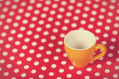 Cup of a coffe on polka dot cover — Stock Photo