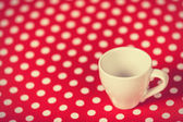 Cup of a coffee on polka dot cover.  — Stock Photo