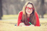 Teen girl with a pen lying down on a grass. — Stock Photo