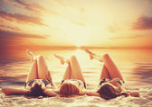 Three girls on the beach in sunset. — Stockfoto