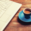 Cup of coffee and laptop on wooden table. — Stock Photo #42874899