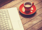 Cup of coffee and laptop on wooden table. — Stock Photo