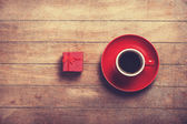 Little red gift and cup of the coffee.  — Stock Photo