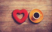 Cup of coffee and shape heart on a wooden table. — Stock Photo