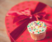 Cream cake with gifts on a wooden table. — Stock Photo