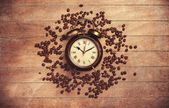 Alarm clock and coffee beans on a wooden table. — Stock Photo
