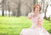 Beautiful women in dress sitting on a spring grass. — Foto Stock